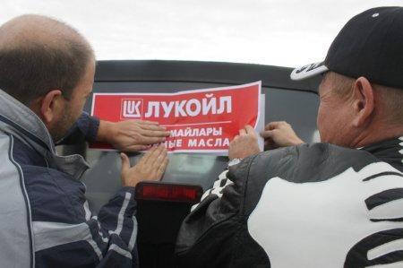 Участники ралли-кросса клеят рекламу спонсора мероприятия