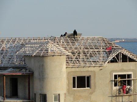 В Актау на крыше частного коттеджа строители работают без страховки