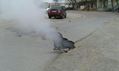 После проводимых испытаний теплопроводных сетей в 6 микрорайоне провалилась часть дороги перед домом #32.